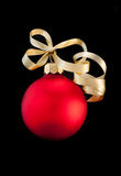 One red satin Christmas ball with gold ribbon. On black background Stock Photos