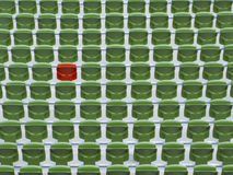 One red seat in rows of empty, green stadium seats Stock Image