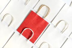 One red shopping bag in background of white bags isolated on white background. Shopping and sales concept stock images