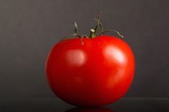 One red tomato. One big red shiny tomato on a dark gray background Stock Photo