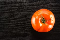 Fresh Raw tomato La parcela variety on black wood. One red tomato isolated on black wood background top view Royalty Free Stock Image