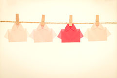One Red among white origami shirt paper hanging  on rope , uniqu Stock Photography