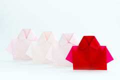 One Red among white origami shirt paper , unique individuality a Stock Images