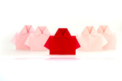 One Red among white origami shirt paper , unique individuality a Royalty Free Stock Images