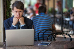One relaxed young handsome professional businessman working with his laptop, phone and tablet in a noisy cafe. stock photo