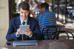 One relaxed young handsome professional businessman working with his laptop, phone and tablet in a noisy cafe. Stock Image