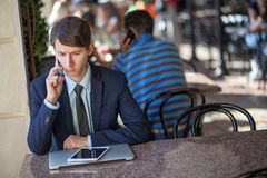 One relaxed young handsome professional businessman working with his laptop, phone and tablet in a noisy cafe. Developed from RAW. retouched with special care royalty free stock images