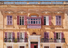 One of the residential houses in Mdina, Malta. View of one of the residential houses in Mdina with traditional Maltese style open balconies and red shutters Royalty Free Stock Images