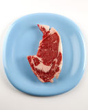 One Rib Eye Steak on a Blue Plate. Photograph of one rib eye steak on a blue plate stock photos