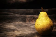 One ripe bosc pear on gray studio backdrop stock photo