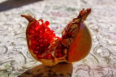 One ripe opened pomegranate fruit closeup. One ripe opened pomegranate fruit lying on a tablecloth with back lighting close-up Stock Images