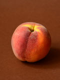 One ripe peach. On a brown background Royalty Free Stock Photo