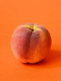 One ripe peach. On orange colored background Stock Photos