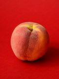 One ripe peach. On a red background Royalty Free Stock Photo