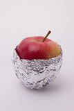 One ripe red apple wrapped in foil on a white background. One ripe red apple beautiful wrapped in foil on a white background Stock Photography