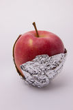 One ripe red apple wrapped in foil on a white background. One ripe red apple beautiful wrapped in foil on a white background Royalty Free Stock Photos