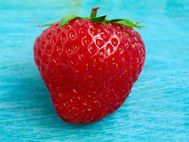One ripe strawberry. On a blue background Royalty Free Stock Photos