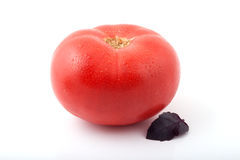 One ripe tomato with a basil leaf Stock Photos