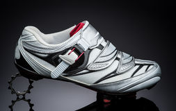One road cycling shoe standind at small metal sprocket. Over dark background royalty free stock images