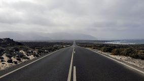 One road in lanzarote. A massive road of lanzarote crossing the island. On the side we can see the beach and the sea and in the end the mountains Stock Photos