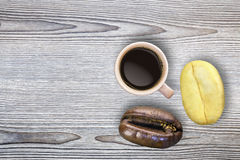One roasted and one raw coffee bean and a brown earthenware coff Stock Photo
