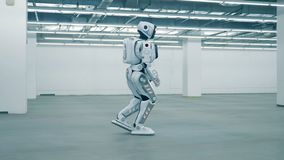 Modern cyborg walking in a room, side view. One robot walks in a room stock footage
