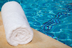 One rolled-up white towel by blue pool Stock Images