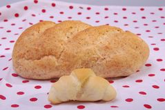 One rolls and big bread. Small croissant and a large loaf of whole-wheat flour on the tablecloth with red dots. Very close, you can see the structure of pastries stock images