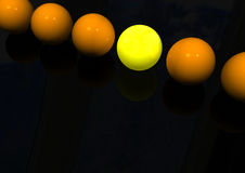 One In A Row. One special yellow ball standing out against a line of similar orange balls Stock Image
