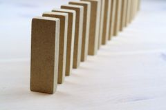 One row of rectangular wooden bars standing upright. Light background stock image