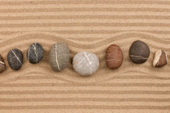 One row of stones lying on the sand, with space for text. Stock Photography