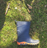 One rubber boot on grass with daisy Royalty Free Stock Photo