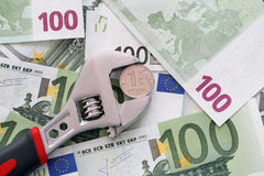 One ruble coin grip in a adjustable wrench on euro banknotes Stock Photography