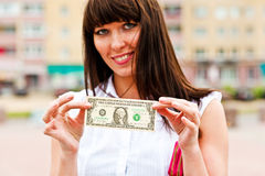 One's bottom dollar. A woman holding a one dollar Stock Images