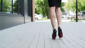 Businessperson on the high heel goes to workplace