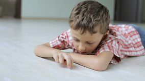 One sad little boy lying on the floor at home  at the day time. Sad little boy lying on the floor at home  at the day time. Concept of sorrow stock footage