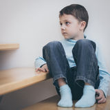 One sad little boy sitting on the stairs in house at the day tim. E. Concept of sorrow royalty free stock image