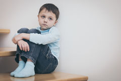 One sad little boy sitting on the stairs in house at the day tim. E. Concept of sorrow stock image