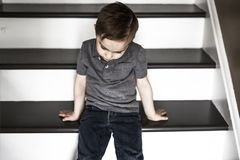 One sad little boy sitting on the stairs in house at the day time. Stock Photography