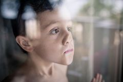 One sad little boy standing near the window at the day time. Concept of sorrow royalty free stock photography
