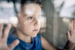 One sad little boy standing near the window at the day time. Concept of sorrow royalty free stock images