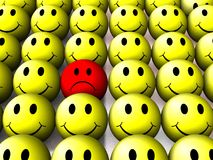 One sad smiley. A sad face smiley in a large group of happy smiling smileys vector illustration