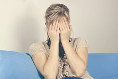 One sad woman sitting on the sofa and holding her head in her hands Stock Photos