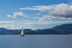 One sailing boat on water with lefkas shore mountains and clouds Royalty Free Stock Photos