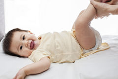 A small cute little baby girl was lying down, her diaper was being changed by her father Stock Photos
