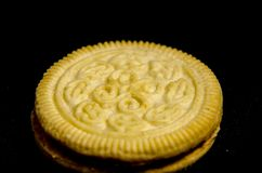 One sandwich   cookie  looking for you. A cookie is a baked or cooked food that is small, flat and sweet. It usually contains flour, sugar and some type of oil Stock Photo