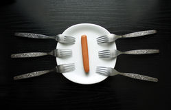 A one sausage on a plate. With many forks Stock Photos