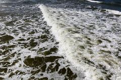 One sea wave on a water surface. Dark Baltic Sea waters and one wave on its surface. This can be seen close to seashore during windy day in Kolobrzeg in Poland Stock Photos