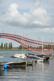 One section of modern red pedestrian bridge over the river Stock Images