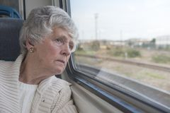 One senior woman looking out of the window stock photography